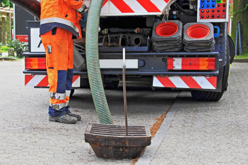 A septic professional using a hose from their truck to clear a sewage backup