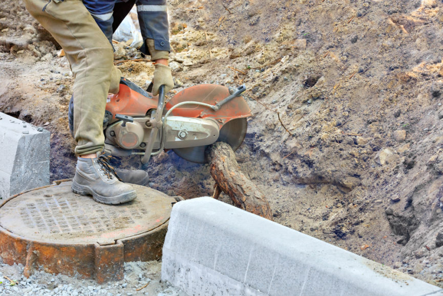 Specialist removing a tree root from a sewage line